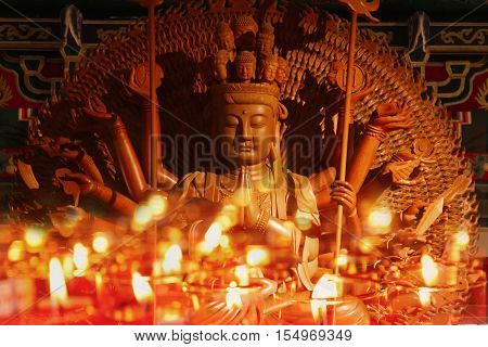 Guan Yin sculpture Thousand Hand carved of wood with candle light
