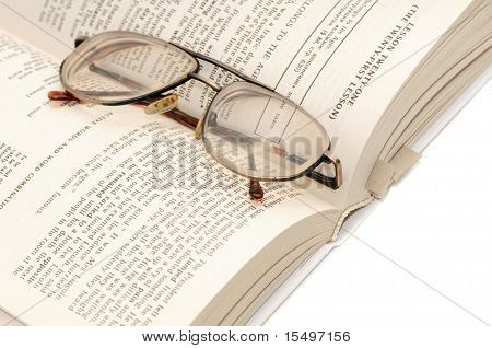 book and glasses isolated on a white background