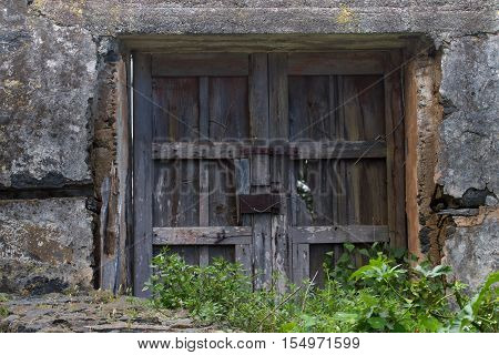 Old wooden door or gate and metal wires of the rusted lock. Outside the house, village, nature, everything comes into disrepair