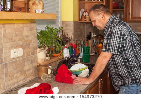 Home work in the kitchen. Man washing dirty dishes in the kitchen sink. Domestic cleaning up after the party. Husband cleans the dishes.