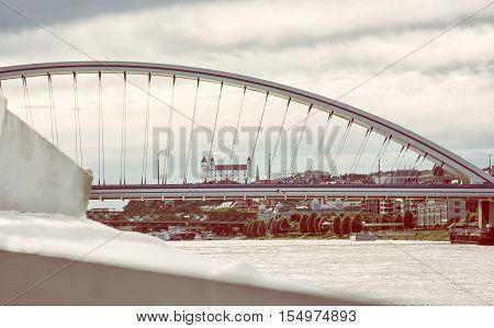 Bratislava castle behind modern Apollo bridge. Cruise on the Danube river. Ship transportation. Architectural theme. Retro photo filter. Travel destination.