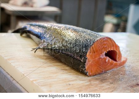 Salmon carcass lies on a chopping board in the fish shop before cutting fillets. Salmon before cutting fillets. Horizontal. Daylight.