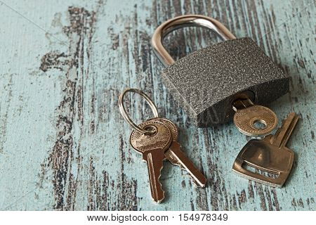 Keys and the lock on a blue wooden background.