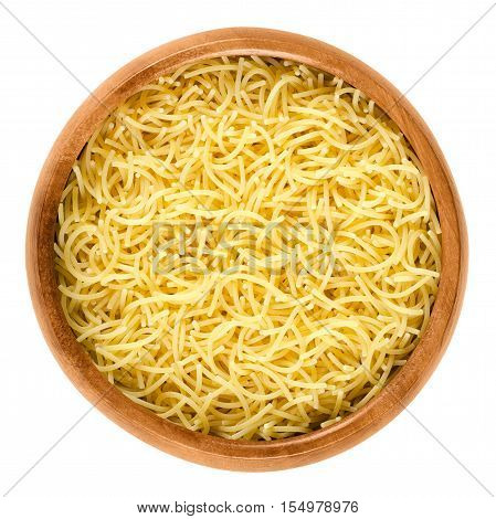 Filini short cut pasta in wooden bowl. Italian miniature noodles with little threads, prepared with eggs. Uncooked dried durum wheat semolina pasta. Isolated food macro photo over white background.