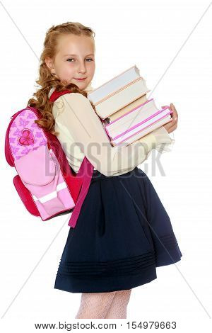 Beautiful small girl schoolgirl in black skirt and white blouse goes to school. Behind the girl a big red schoolbag , holding her stack of books. Close-up.Isolated on white background.