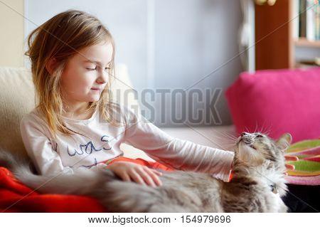 Little Preschooler Girl In Pajamas And Her Cat