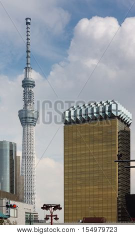 Tokyo Japan - September 26 2016: Asahi Beer Company headquarters supposedly looks like a glass of lager beer with tall Skytree tower in the distance under blue cloudy sky.