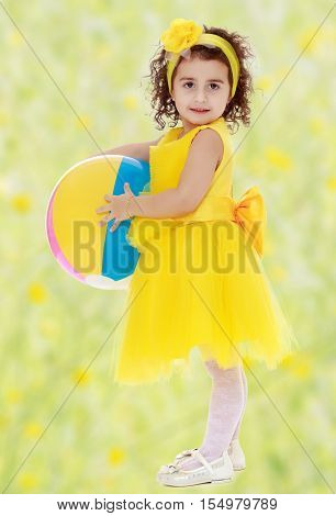 Pretty dark-haired little girl in a bright yellow dress and a bow on my head with a striped ball. Girl posing sideways to the camera in full growth.Bright, floral yellow-green blurred background.