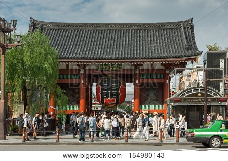 Tokyo Japan - September 26 2016: The vermilion painted Kaminarimon gate of Senso-ji Buddhist Temple stands close to the main road and is the gate most visitors pass through. Lots of people. Blue cloudy sky.