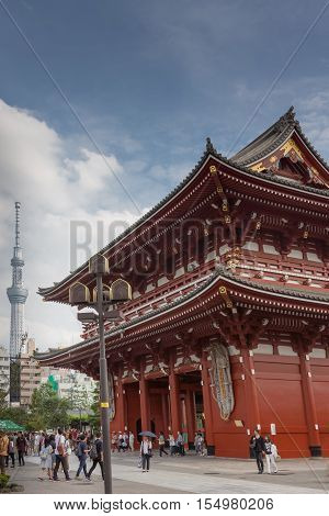 Tokyo Japan - September 26 2016: Vermilion and gold painted Hozomon Gate at Senso-ji Buddhist Temple with tall Skytree tower in the distance under blue cloudy sky. Lots of people. Blue cloudy sky.