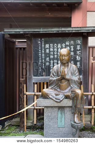 Tokyo Japan - September 26 2016: Closeup of bronze statue of young praying or meditating Bodhisattva at Senso-ji Buddhist Temple. Sits on pedestal. Signs in background.
