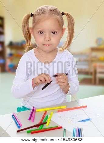 Pretty little blonde girl drawing with markers at the table.Girl holding in hands blue marker.The concept of pre-school education of the child among their peers .