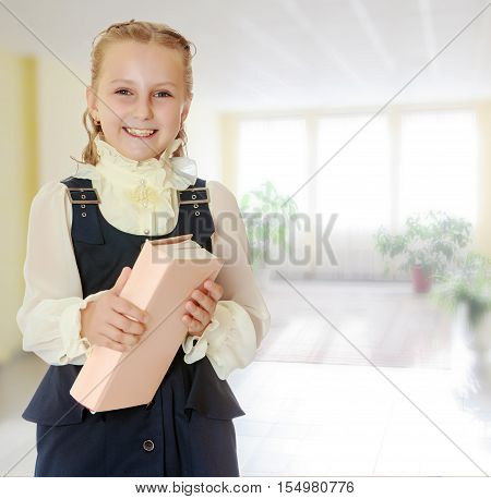 Dressy girl schoolgirl in black dress and white blouse holding a textbook and smiling cheerfully at the camera. Close-up.In the room with the big bright window in the wall.