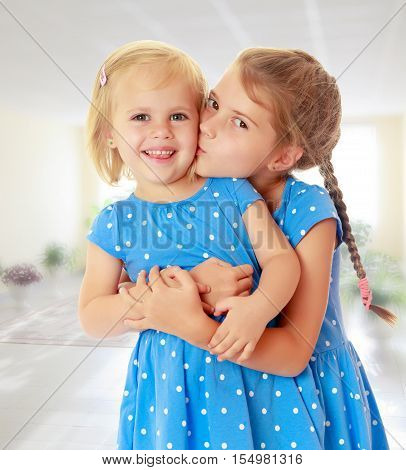 Two charming little girls, sisters , in identical blue dresses with polka dots. Older sister kissing the younger on the cheek.On the background of the school hall with large Windows.