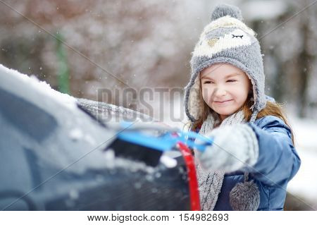 Adorable Little Girl Helping To Brush A Snow