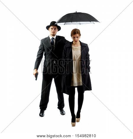 An elegant lady with a bodyguard holding a gun and a black umbrella