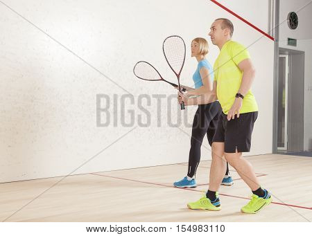 young caucasian man and woman playing squash.