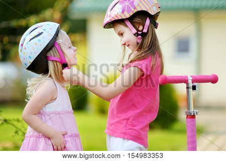 Little Girl Helping Her Sister To Put A Helmet On