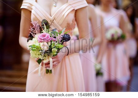Row Of Bridesmaids With Bouquets At Wedding