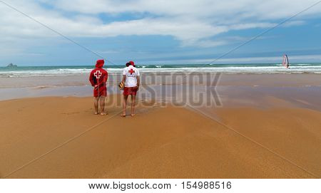 ORINON SPAIN - JULY 6 2016: Two unknown rescuers on the deserted sandy beach. Rescuers in red-white clothes stand facing the ocean. In waves the sail from a board is in the distance visible.