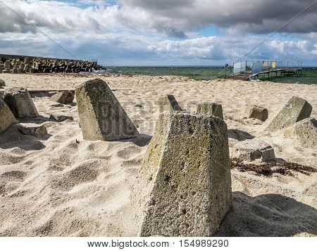 Massive concrete breakers stacked on the beach