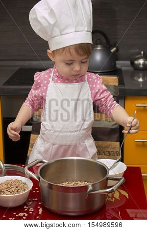 little cute girl playing in the kitchen with a ladle and saucepan