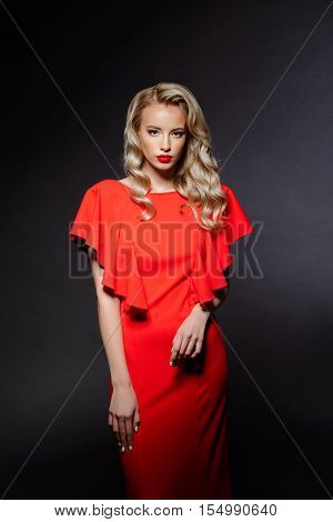 Young beautiful blonde girl in red evening dress posing, looking at camera at party over grey background. Copy space.
