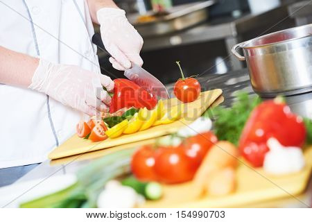 cook chef hands with knife preparing salad food in commercial kitchen