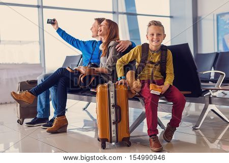 Time with family is time well spent. Little smiling boy sitting at airport and holding tickets in his hand with his parents making selfie in background