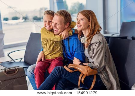 Family life is about fun. Photo of smiling happy family sitting in airport departure lounge and waiting to go on vacation