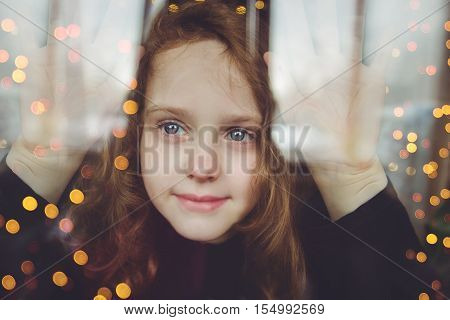Young girl looking on windows shopping with illuminated christmas garland. Shopping black friday sale.