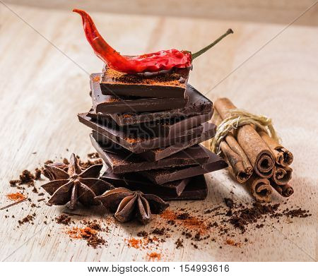 Condiment Still Life. Cayenne Pepper with Anise Star Cinnamon and Chocolate Bar Stack.