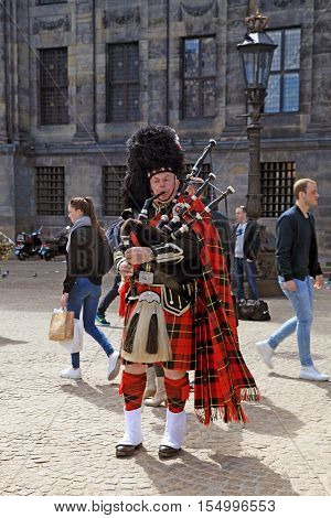 AMSTERDAM, NETHERLANDS - MAY 3, 2016: Street musician with Scottish traditional bagpipes on the Dam Square, Amsterdam, Netherlands.