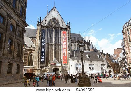 AMSTERDAM, NETHERLANDS - MAY 3, 2016: Tourists in front of the Nieuwe kerk (New church) located on Dam square used for exhibition space and as museum in Amsterdam, Netherlands.