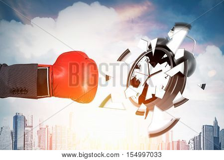 Businessman's hand in red boxing glove is smashing giant alarm clock against cityscape background. Concept of deadline. Toned image