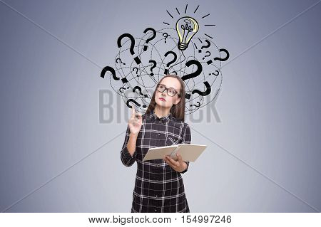 Nerdy girl is holding her notebook and standing near dark gray wall with question marks and light bulb sketch on it. Concept of bright idea