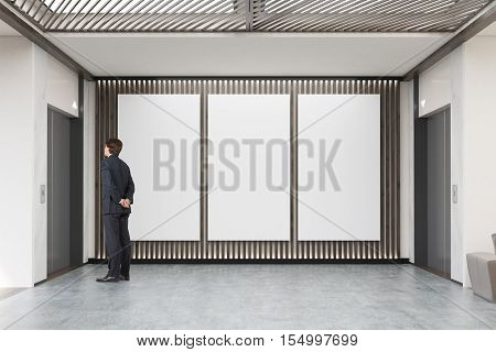 Man waiting for the elevator in company lobby with three vertical posters and two elevators. Concept of modern waiting area design. 3d rendering. Mock up.