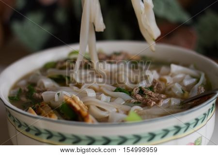 Vietnamese beef noodle soup Pho Bo with garnish of leaves of cilantro, Asian basil and bean sprouts on kitchen table. Young woman is cooking in background. Traditional healthy food.