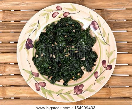 Sauteed fresh organic baby spinach with raw pine nuts on ceramic plate and bamboo table