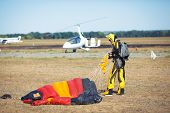 Skydiver with red parachute after landing on the ground. poster