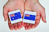 Two hands holds the national flags of Australia (R) and New Zealand (L) beside each other on a white background. Foreign relationship policy concept poster