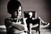 Old style photography: angry boy standing in front of relaxed girl in chair. Black and white photo, darkness, and a lot of grain added for desired effect. poster