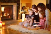 Happy young family using a tablet pc at home by a fireplace in warm and cozy living room on winter day poster