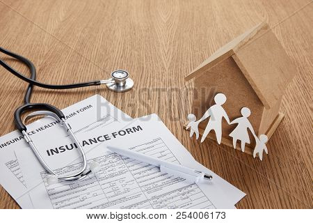 Close-up View Of Insurance Form, Insurance Health Claim Form, Pen, Stethoscope, House Model And Pape