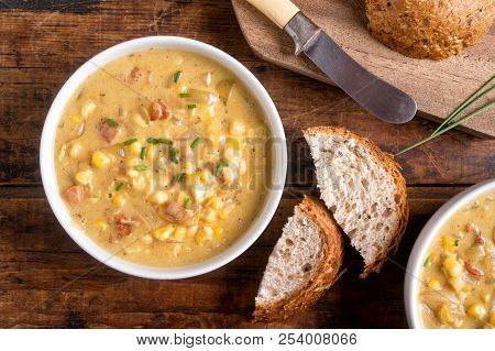 A Bowl Of Delicious Homemade Bacon Corn Chowder With Whole Grain Bread On A Rustic Wood Table Top.
