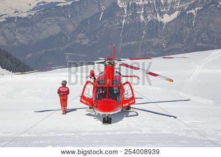 FLUMSERBERG - MARCH 25: The unidentified pilots of the swiss emergency service Rega performing training exercise in skiing area Flumserberg, Switzerland on March 25, 2018.