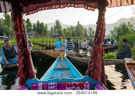 Srinagar, India - June 16, 2017: Unidentified vegetable sellers taking their produce to the floating market in the morning on Dal Lake in Srinagar, Kashmir. View from the traditional shikara boat