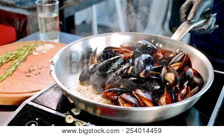 Hissing and steaming mussels in frying pan, close-up poster