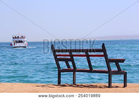 Empty Bench Near Sea And Shipped Ship. Loneliness. Departure Of Ship. Bench Near Beach