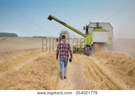 Rear View Of Handsome Farmer With Tablet Walking In Front Of Combine Harvester During Harvest In Fie